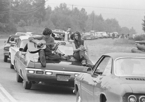 A couple play the guitar sitting on their car on the way to the Woodstock Festival, August 1969. © Iconic Images/Baron Wolman