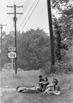 A group of young women sit on the grass next to the 17B West Road at the Woodstock Music & Art Fair, Bethel, NY, August 15, 1969. © Iconic Images/Baron Wolman