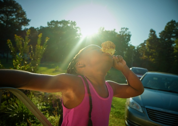 Cousin Miyah devours a caramel apple just days before Halloween. Dalark, Arkansas. Part of the series, Not Forgotten: An Arkansas Family Album, an intimate exploration of loss, love and tradition in a rural black community.